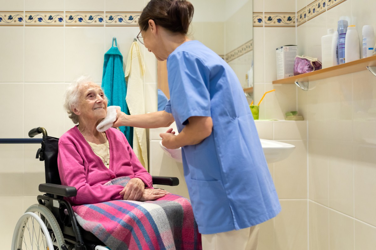 Female personal care worker washes the face of an elderly wheelchair-bound woman