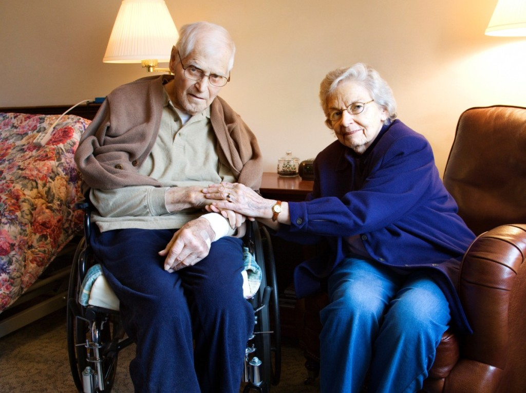 Elderly Caucasian couple in bedroom at retirement community center.