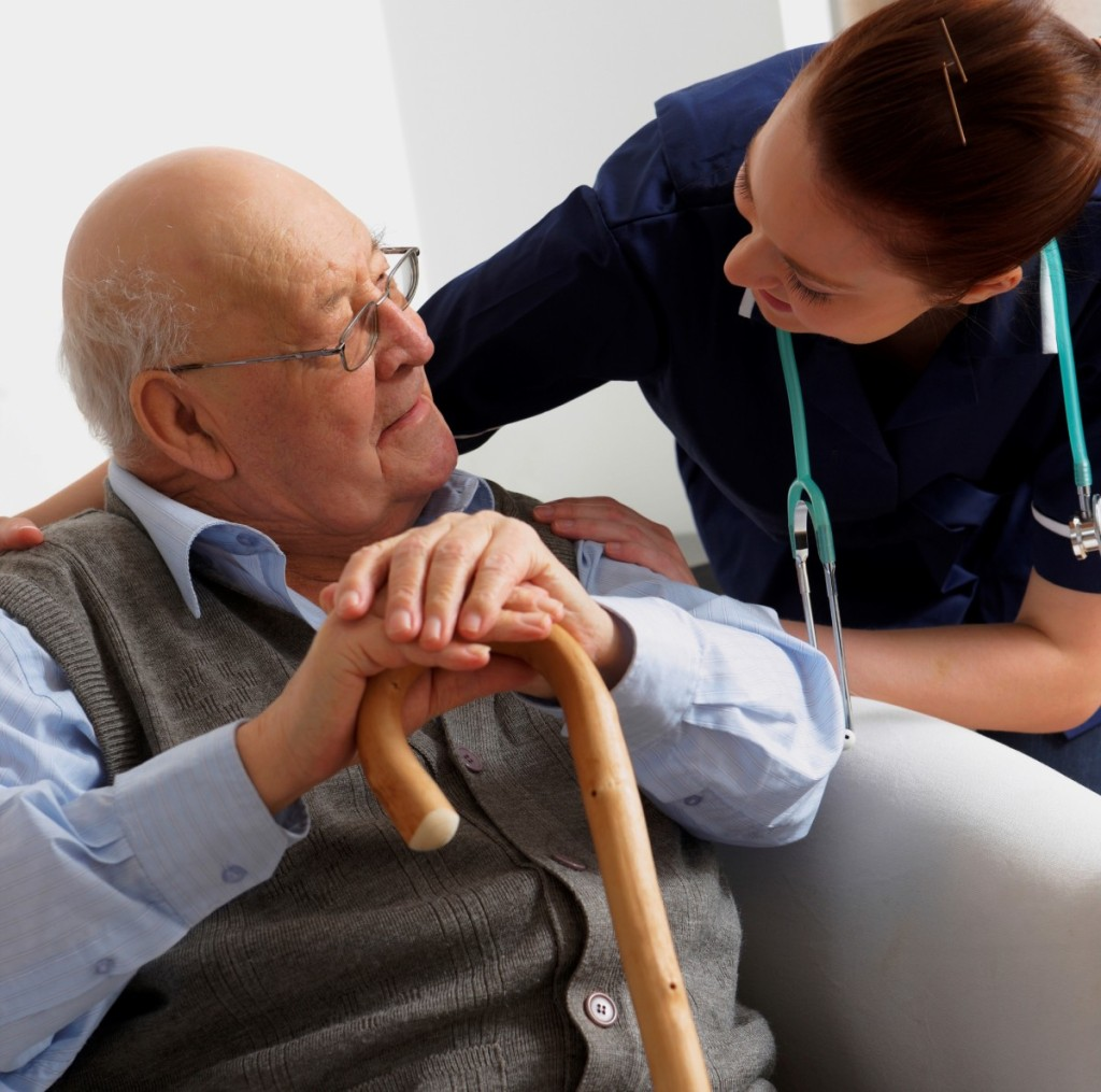 Senior man being visited by a nurse at home