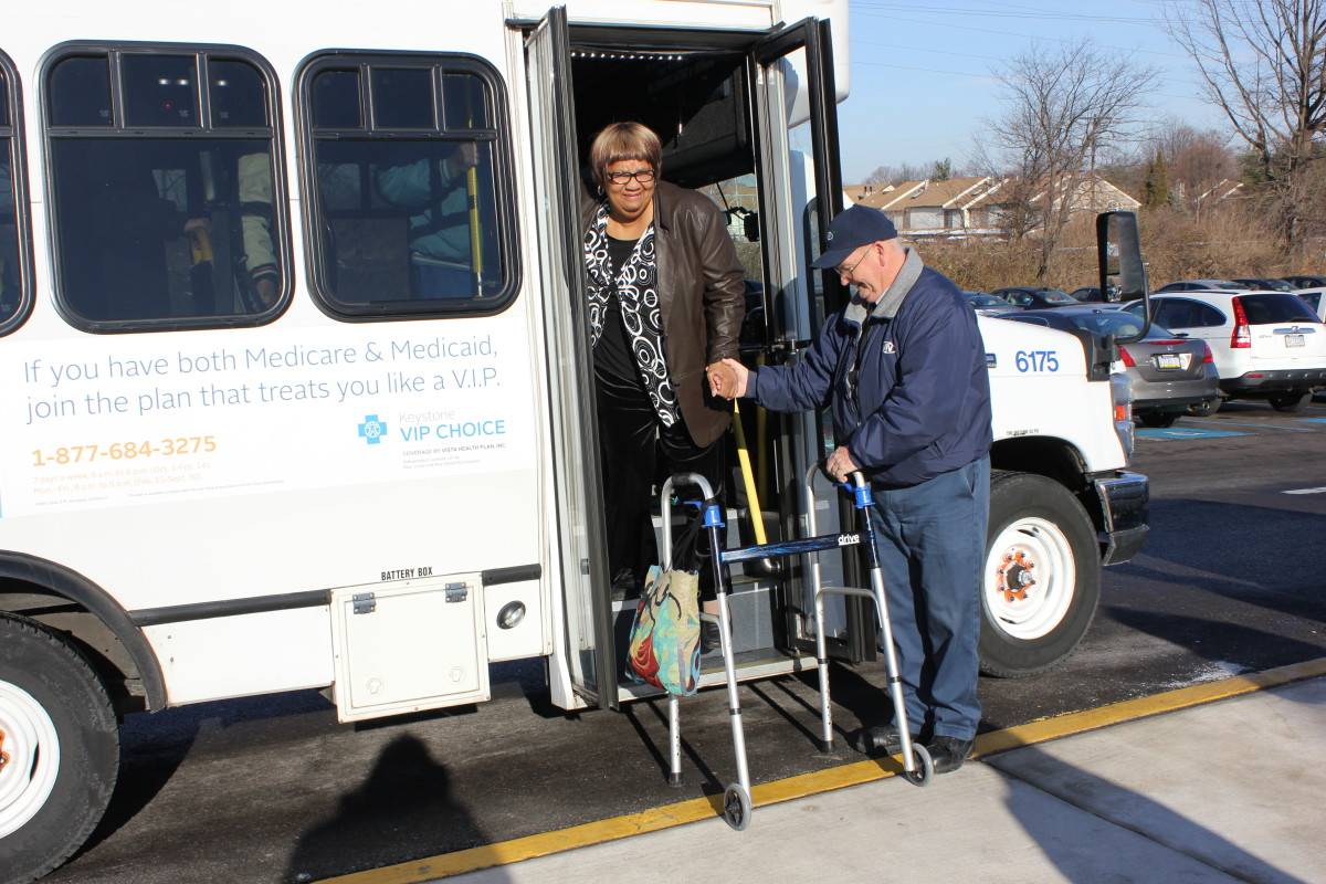 Shared ride driver helps an elderly woman with a walker out of a Shared Ride van.