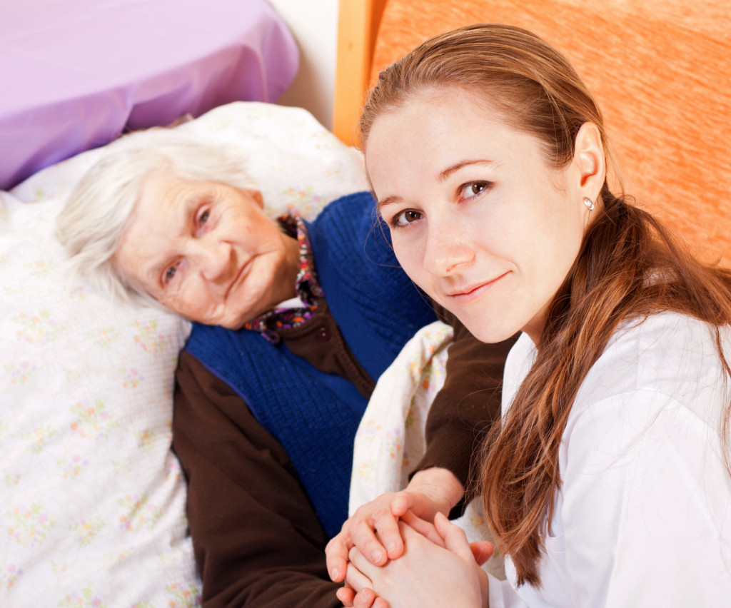Young woman holds the hand of an elderly woman who is lying in bed.