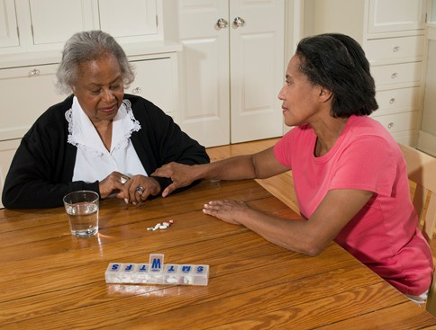 Older adult and caregiver with medication.