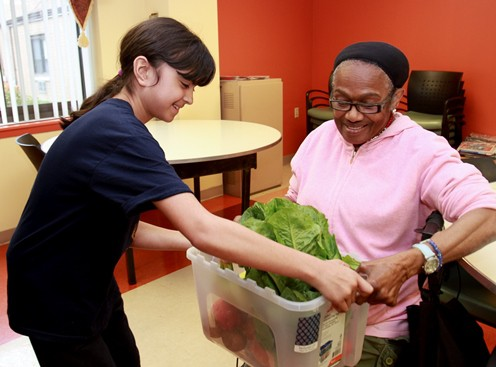 Receiving a produce delivery from volunteer Sarah Martínez is Lenora S. Ward, a member of the food buying club run by the Asociación Puertorriqueños en Marcha.