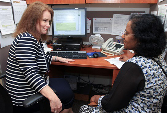 Joanne Burke (left), manager of the Apprise program at Einstein Medical Center Philadelphia, counsels a client new to Medicare. (Photo by Paola Nogueras)